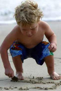 beautiful boy drawing in the sand at the beach