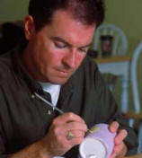 man painting pottery for therapeutic artwork