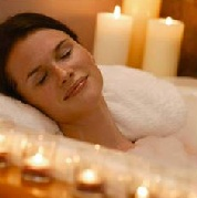 woman relaxing in bathtub with candles