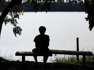 Lonely man sitting by a lake, lost in thought