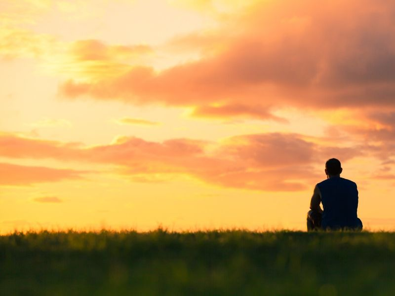 Man sitting on grass, looking at a fiery sky