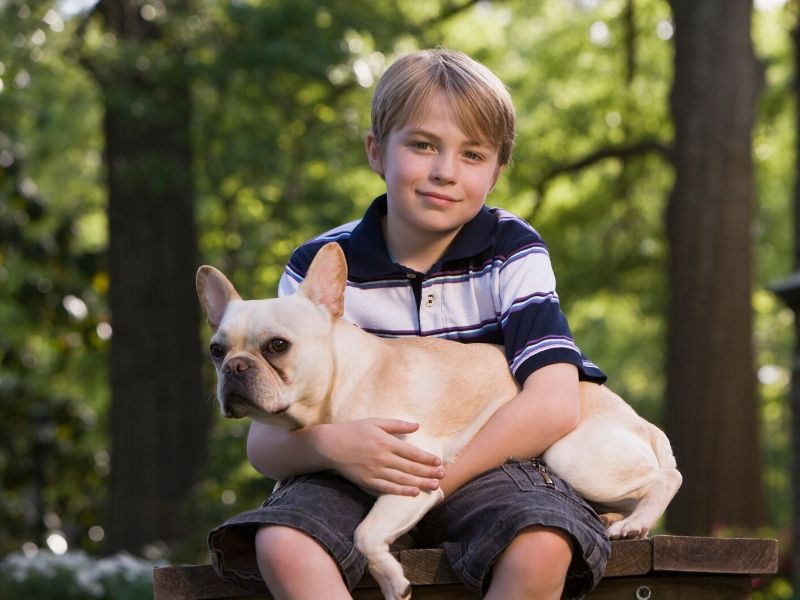 Young boy holding his dog