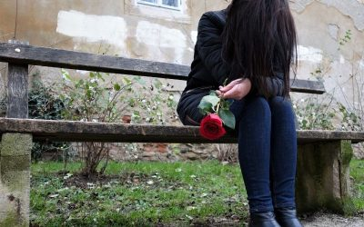 Grieving woman sitting on a bench with a rose in her hand