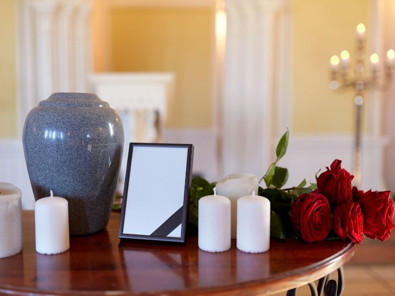 Urn set up with candles and roses on a table
