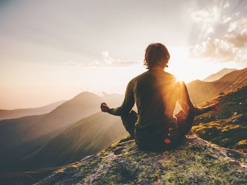 Man meditating on a mountain top
