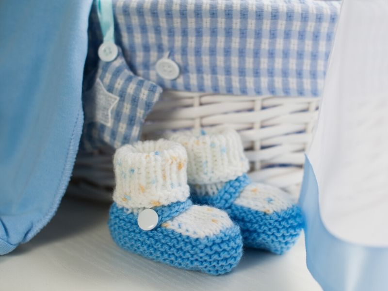 Blue baby shoes in front of a hamper