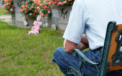 Man sitting on a bench by the grave