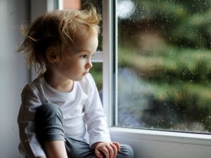 Sad little girl looking out the window longingly