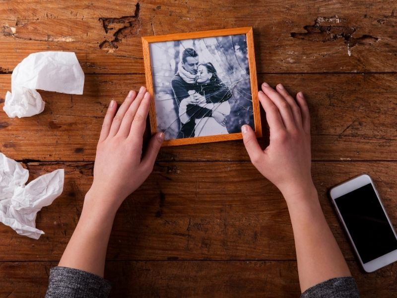 Woman holding broken picutre frame with couple