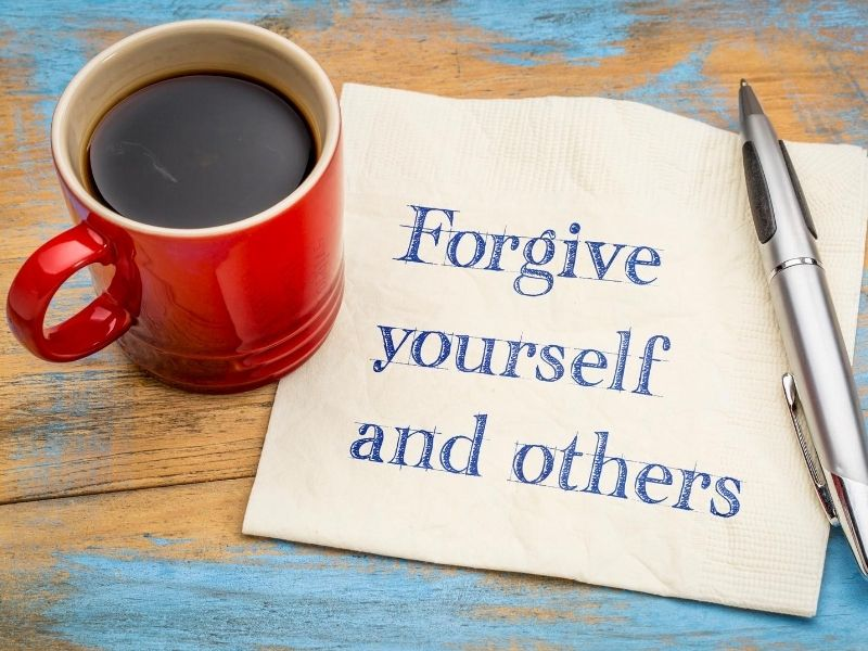 Red mug on top of a napkin with a message: forgive yourself and others