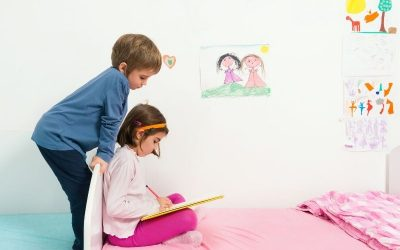 Girl sitting in bed drawing and brother watching over her shoulder