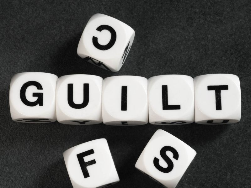 The word guilt spelled with scrabble pieces