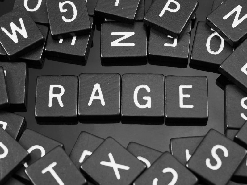 The word rage spelled with black scrabble tiles