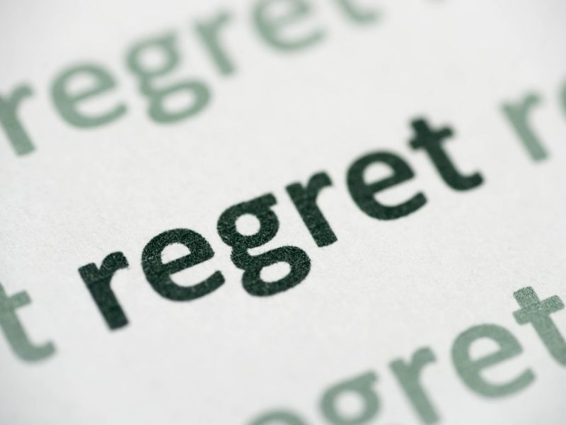 The word regret typed on paper