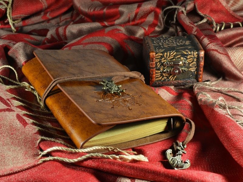 A grief journal and memory box sitting on a red shawl